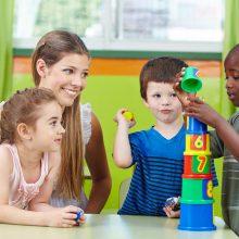 Children,With,Nursery,Teacher,Building,Tower,In,A,Kindergarten,Group