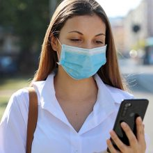 Covid-19,Mobile,Application,Young,Woman,Wearing,Surgical,Mask,Using,Smart